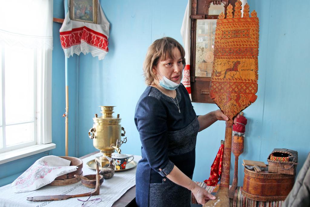 Вмузейной народной избе: Анна Фатьянова показывает прялку спалащельской (мезенской) росписью